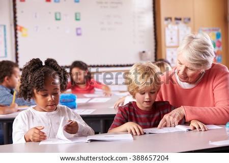 Senior teacher helping elementary school pupil in class - stock photo