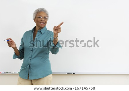 Senior teacher pointing while gesturing against white board in classroom - stock photo