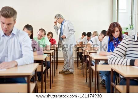 Senior teacher with class in a classroom - stock photo