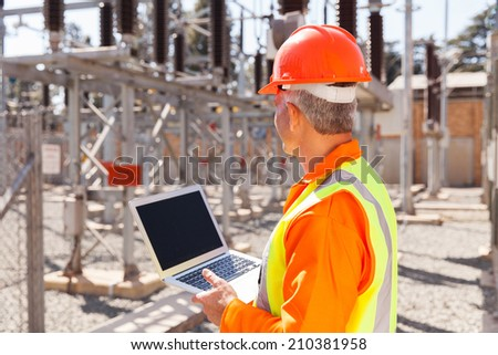 senior technician holding laptop computer in substation - stock photo