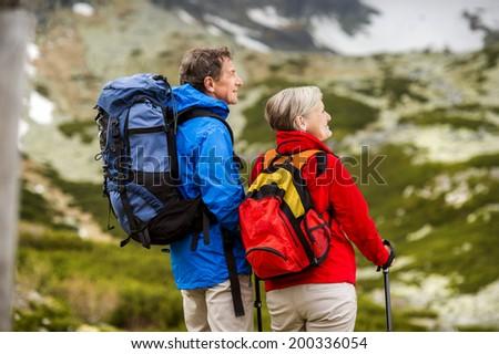 Senior tourist couple hiking at the beautiful mountains - stock photo