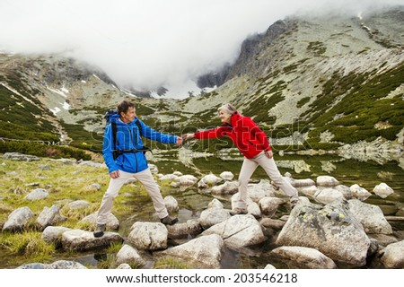 Senior tourist couple hiking at the beautiful mountains, tarn in the background - stock photo