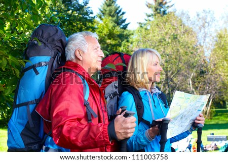 Senior Tourist couple with backpacks in the park. - stock photo