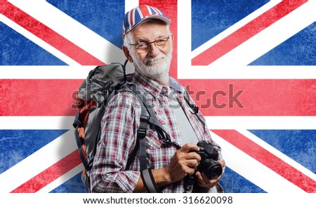 Senior tourist photographer with backpack and digital camera, he is wearing a British flag cap