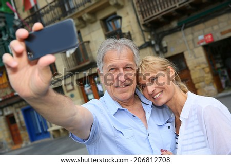 Senior tourists taking picture of themselves with smartphone - stock photo