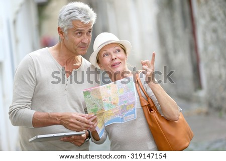 Senior tourists walking in street with map and tablet - stock photo