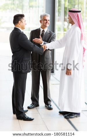 senior translator introducing muslim businessman to business partner - stock photo