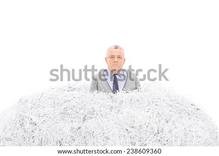 Senior trapped in a pile of shredded paper isolated on white background - stock photo