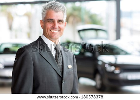 senior vehicle salesman working at a car dealer - stock photo