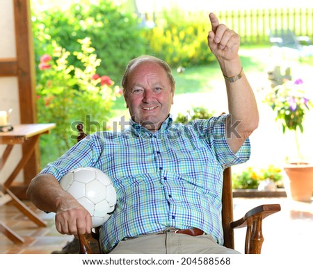 senior watching football match in the tv - stock photo