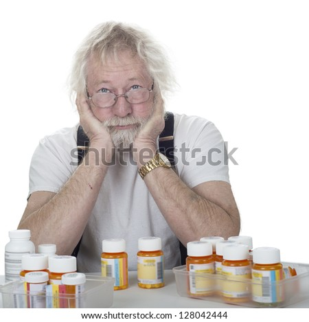 senior wearing glasses with a lot of prescription bottles of pills isolated on white - stock photo