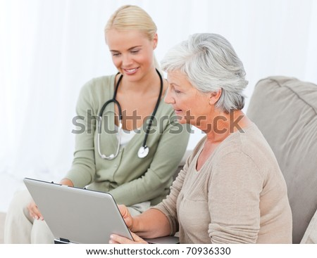Senior with her doctor working on the laptop - stock photo