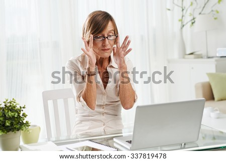 Senior woman adjusting her glasses as she is ready to work