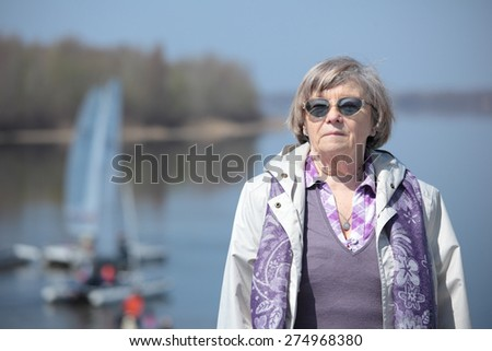 Senior woman against a river in springtime - stock photo