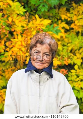 Senior woman against leaves background - stock photo