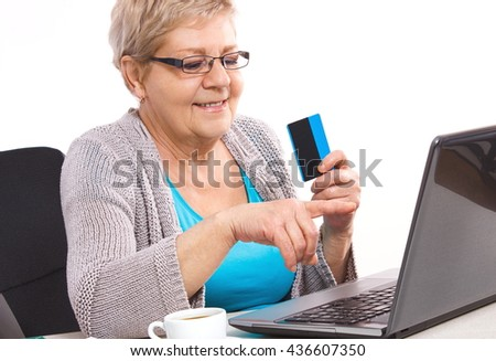 Senior woman, an elderly pensioner holding credit card and showing laptop screen, paying over internet for utility bills or online shopping, surfing internet