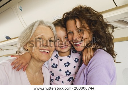 Senior woman and and woman holding girl on airplane - stock photo