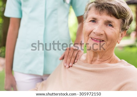 Senior woman and caring nurse in the garden - stock photo