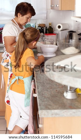 Senior woman and child baking together - stock photo