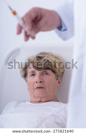 Senior woman and doctor going to do injection - stock photo