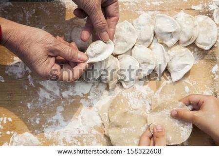 Senior woman and girl making dumplings - stock photo