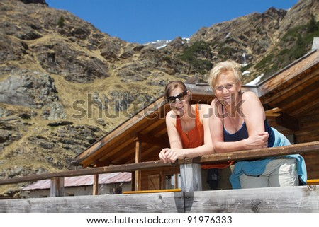 Senior woman and her daughter during a hiking trip in the alps. - stock photo