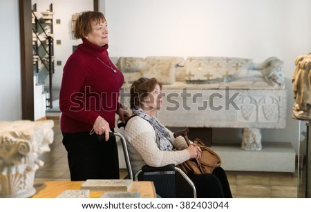 Senior woman and her handicapped female friend at gallery exhibition - stock photo