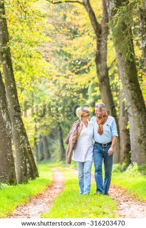 Senior woman and man, a couple, embracing each other having walk in the fall forest