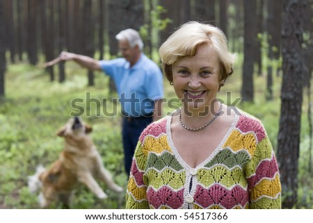 Senior woman and man have fun with a dog in a forest