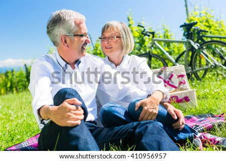 Senior woman and man having picnic on meadow in summer sitting in the sunlight