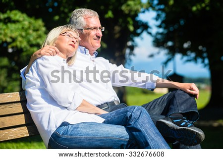 Senior woman and man resting on bench embracing enjoying their vacation - stock photo