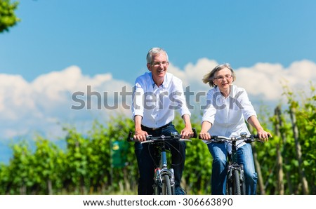 Senior woman and man using bike in summer in vineyard - stock photo