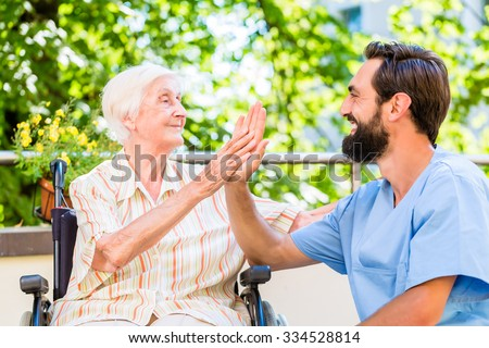 Senior woman and nurse giving High five in nursery home - stock photo