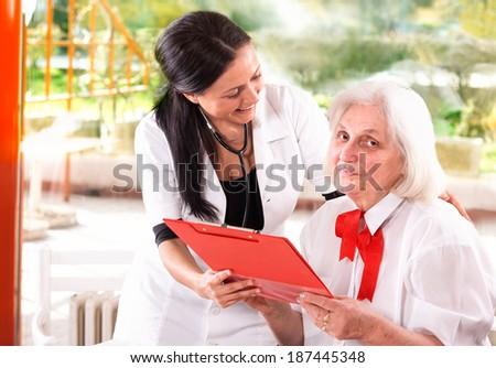 senior woman and nurse  looking at medical report - stock photo