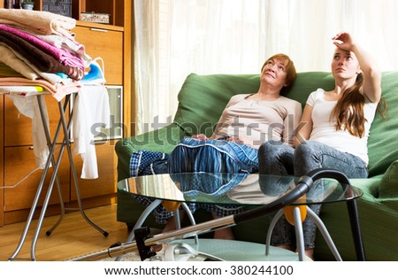 Senior woman and young girl sits on the sofa resting at home.Focus on the left woman - stock photo