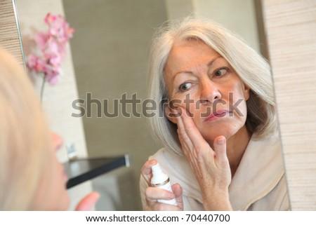 Senior woman applying moisturizer on her face - stock photo