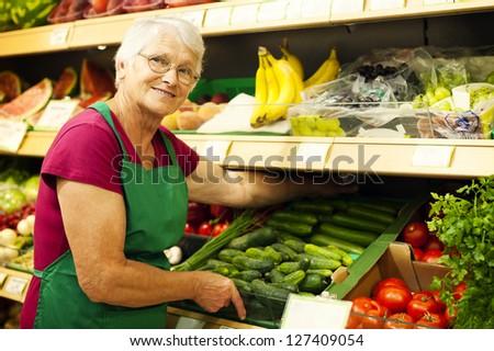 Senior woman arranging vegetables on shelf - stock photo