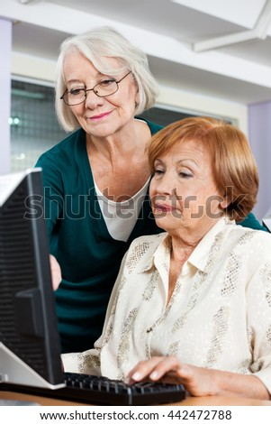 Senior Woman Assisting Friend In Computer Class - stock photo