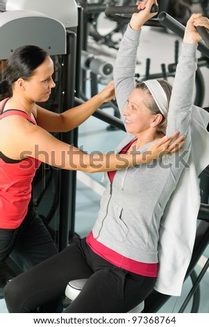 Senior woman at fitness center exercise on machine with trainer - stock photo