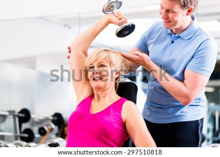 Senior woman at sport exercise with dumbbell in gym with trainer to gain strength and fitness - stock photo