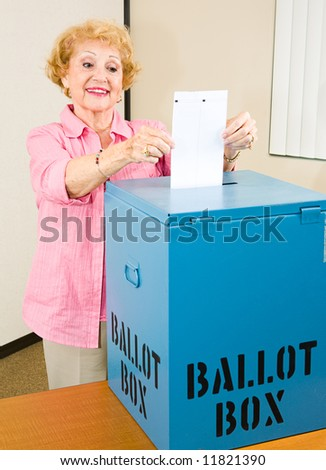 Senior woman at the polls casting her ballot in the box. - stock photo