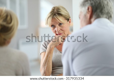 Senior woman attending group therapy - stock photo