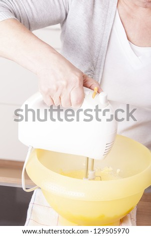 senior woman baking homemade chocolate cake, using a mixer. baking chocolate/stracciatella cake in a glass jar.