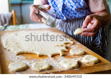 Senior woman baking pies in her home kitchen. Cutting out circles from raw dough.