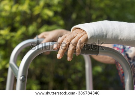 senior woman broken wrist using walker in backyard.
