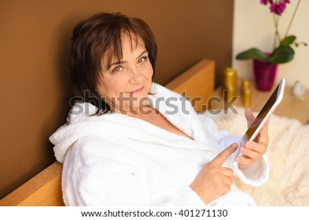 Senior Woman Browsing On Digital Tablet