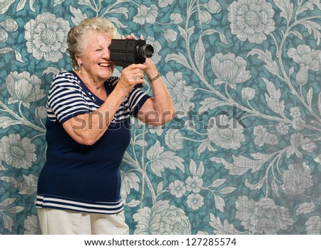 Senior Woman Capturing Photo Against Wallpaper - stock photo