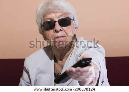 Senior woman changing the TV channel with a remote control - stock photo