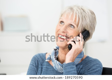 Senior woman chatting on her mobile phone smiling with delight as she listens to the conversation - stock photo