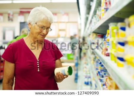 Senior woman checking label on jar - stock photo